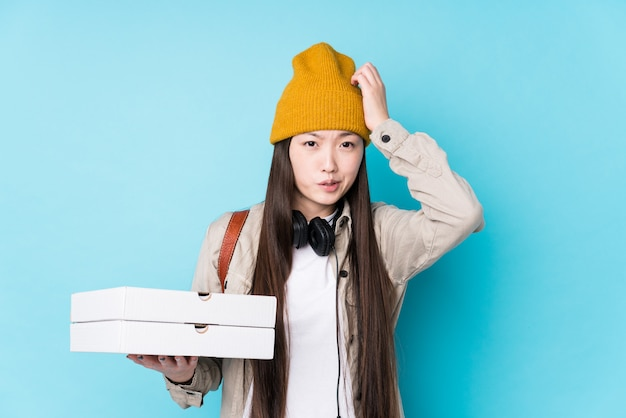 Young chinese woman holding pizzas isolated being shocked, she has remembered important meeting.