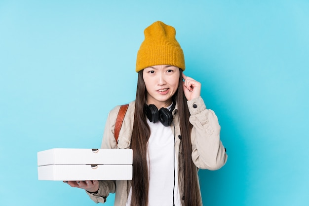 Young chinese woman holding pizzas isolated covering ears with hands.