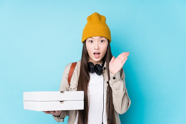 Young chinese woman holding pizzas isolated surprised and shocked.