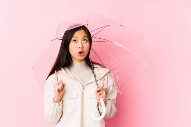 Young chinese woman holding a umbrella isolated pointing upside with opened mouth.