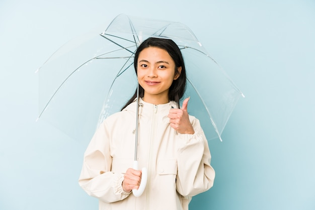 Young chinese woman holding an umbrella isolated smiling and pointing aside, showing something at blank space.