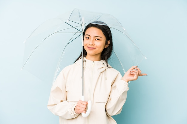Young chinese woman holding an umbrella pointing aside