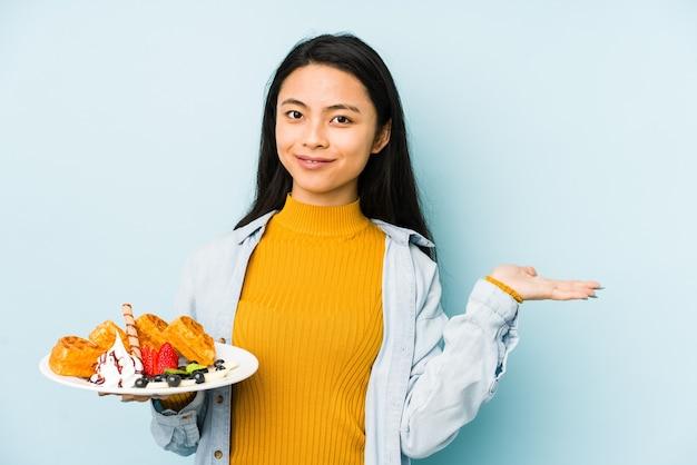 Молодая китаянка, держащая вафлю, изолированную на синей стене, расслабилась, думая о чем-то, глядя на копию пространства.