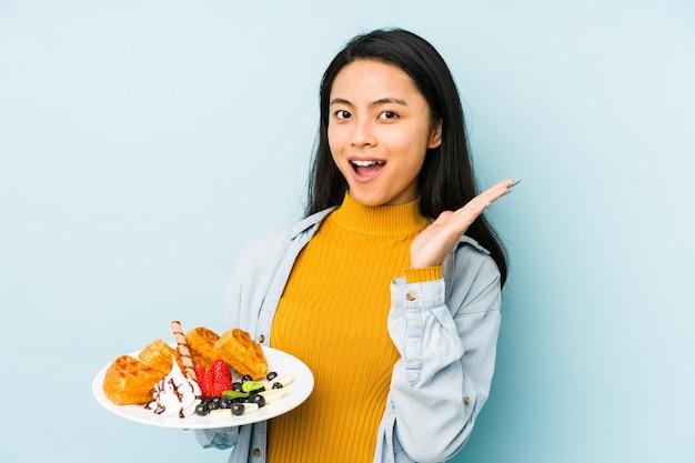Молодая китаянка держит вафлю на синей стене