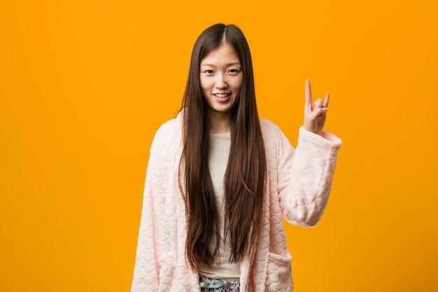 혁명 개념으로 뿔 제스처를 보여주는 파자마에 젊은 중국 여자.