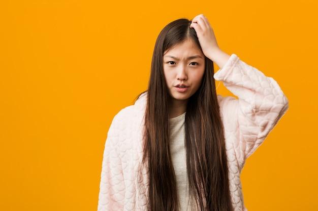 파자마에 젊은 중국 여자는 피곤하고 매우 졸린 그의 머리에 손을 유지합니다.