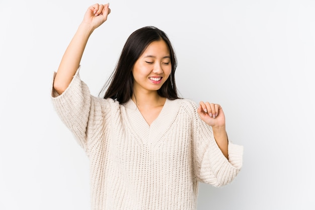 젊은 중국 여자는 특별한 날을 축하하고, 점프하고 에너지로 팔을 올립니다.