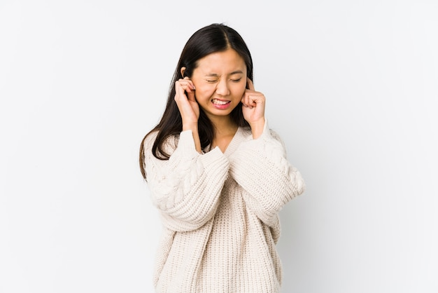 Young chinese woman isolated coning ears with hands.