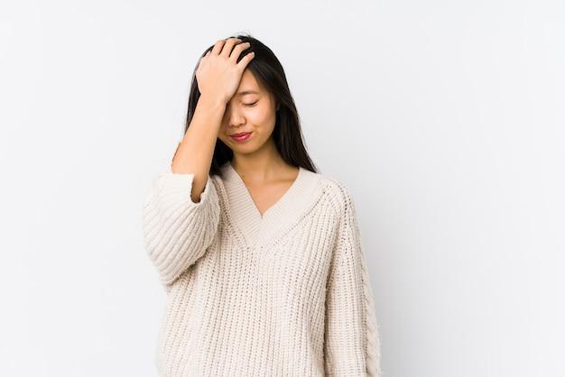 Молодая китайская женщина изолировала забывать что-то, шлепая лоб с ладонью и закрывая глаза.