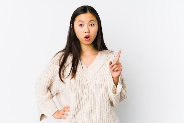 Молодая китаянка изолирована, имея идею, концепцию вдохновения.