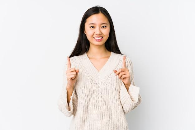 고립 된 젊은 중국 여자는 빈 공간을 보여주는 두 앞 손가락으로 나타냅니다.