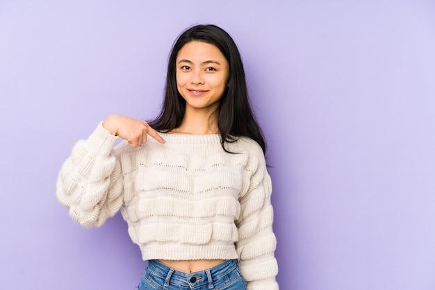 Молодая китаянка изолирована на фиолетовом фоне, человек, указывая рукой на пространство для копирования рубашки, гордый и уверенный
