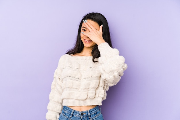 보라색 벽에 고립 된 젊은 중국 여자가 깜박이고 얼굴을 덮고 당황.