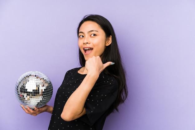 勝利、勝者のコンセプトの後、拳を上げる紫の壁に分離された若い中国人女性。