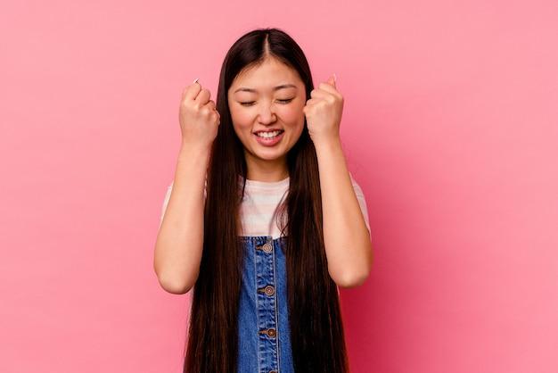 勝利、情熱と熱意、幸せな表現を祝うピンクの背景に孤立した若い中国人女性。