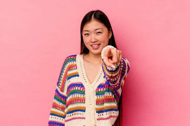 Молодая китаянка, изолированных на розовом фоне, веселые улыбки, указывая на фронт.