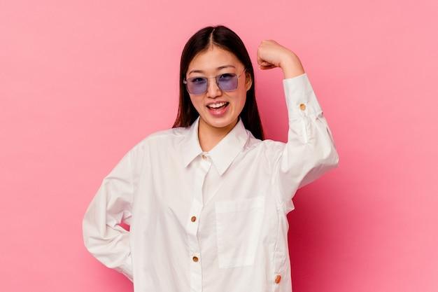 Молодая китаянка изолирована на розовом фоне беззаботно и взволнованно аплодирует. концепция победы.