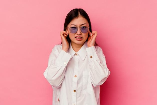 손가락으로 귀를 덮고 분홍색 배경에 고립 된 젊은 중국 여자 스트레스와 큰 소리로 주변에 의해 필사적.