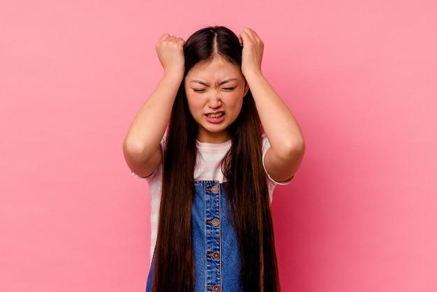Молодая китаянка изолирована на розовом фоне, закрывая уши руками.