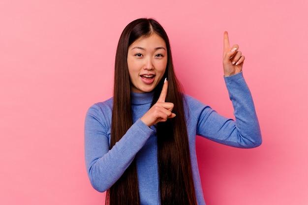 Молодая китаянка изолирована на розовом фоне, танцует и веселится.