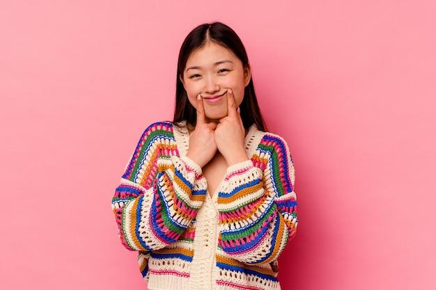두 가지 옵션 사이 의심 분홍색 배경에 고립 된 젊은 중국 여자.
