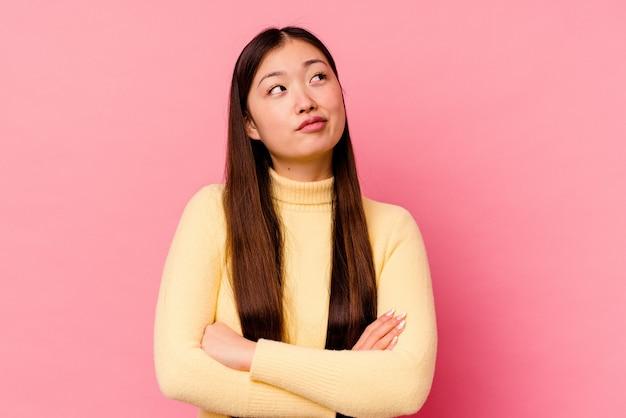 목표와 목적을 달성하는 꿈을 꾸고 분홍색 배경에 고립 된 젊은 중국 여자