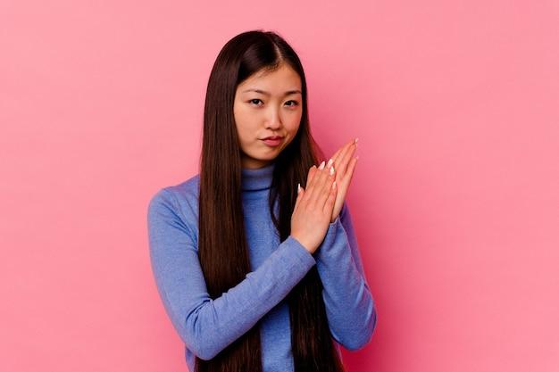 분홍색 배경에 고립 된 젊은 중국 여자는 정력적이고 편안한 느낌, 손을 문지르고 자신감.
