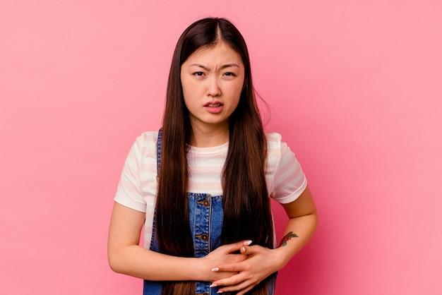 肝臓の痛み、胃の痛みを持つピンクの背景に隔離された若い中国人女性。