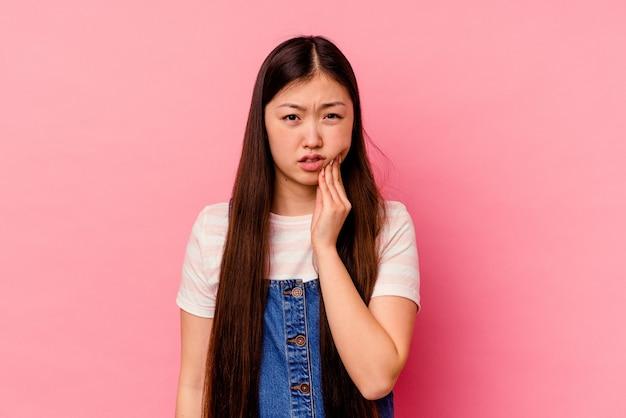 強い歯の痛み、臼歯の痛みを持っているピンクの背景に分離された若い中国人女性。