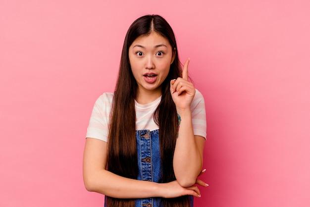 ピンクの背景に隔離された若い中国人女性が、素晴らしいアイデア、創造性のコンセプトを持っている。