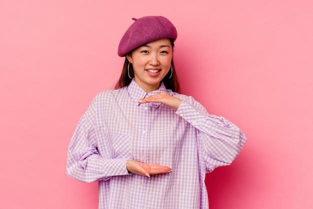 제품 프레 젠 테이 션 양손으로 뭔가 들고 분홍색 배경에 고립 된 젊은 중국 여자.