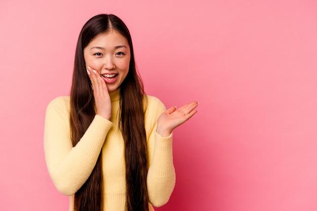 분홍색 배경에 고립 된 젊은 중국 여자 손바닥에 복사 공간을 보유 하 고 뺨에 손을 유지합니다. 놀랍고 기뻐했습니다.