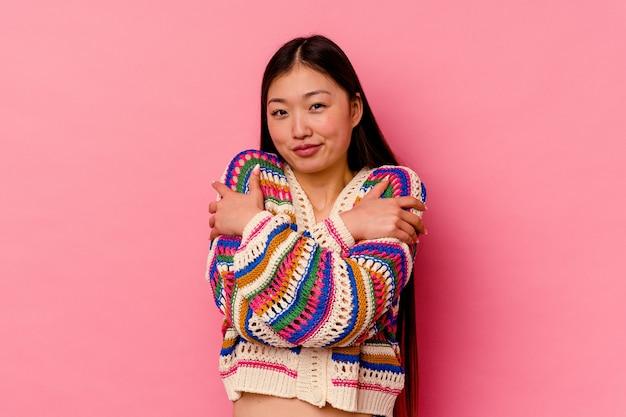 분홍색 배경에 고립 된 젊은 중국 여자 포옹, 평온하고 행복 하 게 웃 고.