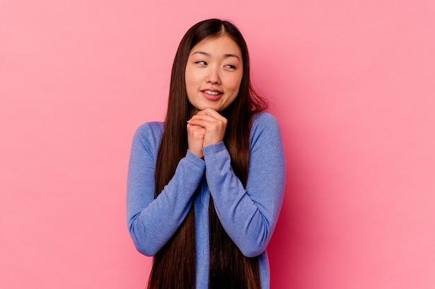 Молодая китаянка, изолированная на розовом фоне, держит руки под подбородком, счастливо смотрит в сторону.