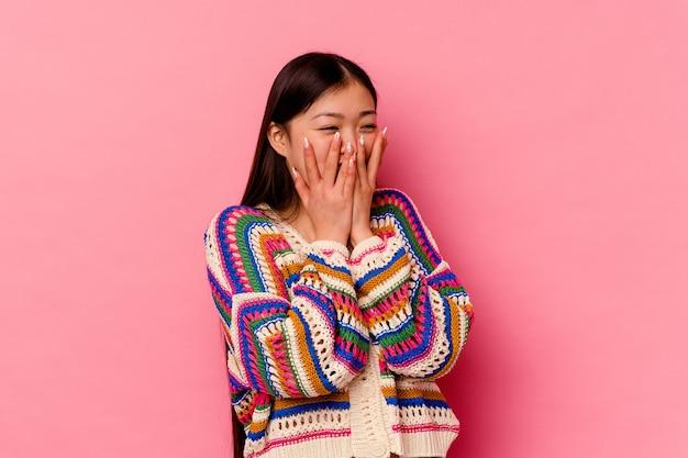 뭔가 대해 웃고, 손으로 입 취재 분홍색 배경에 격리 된 젊은 중국 여자.