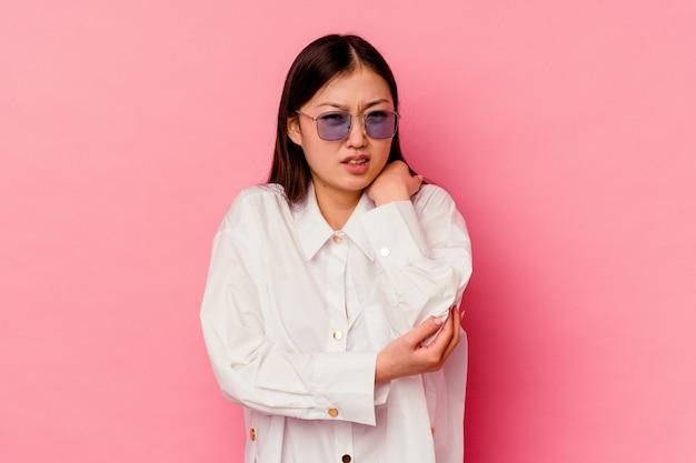 나쁜 움직임 후 고통을 팔꿈치 마사지 분홍색 배경에 고립 된 젊은 중국 여자.
