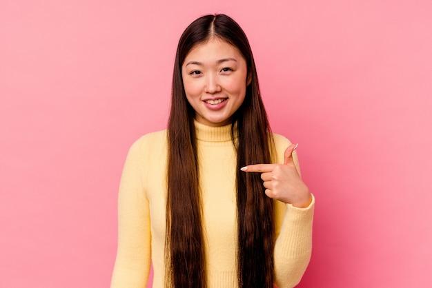 誇りと自信を持って、シャツのコピースペースを手で指しているピンクの背景の人に分離された若い中国人女性