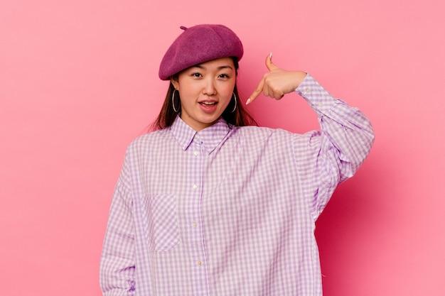 Молодая китаянка изолирована на розовом фоне человек, указывая рукой на пространство для копирования рубашки, гордый и уверенный