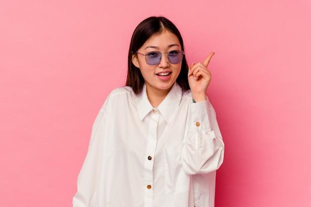 Молодая китаянка изолирована на розовом фоне, указывая на разные места для копирования, выбирая одно из них, показывая пальцем.