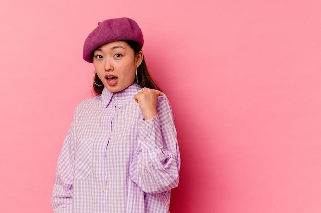 Молодая китаянка, изолированная на розовом фоне, показывает пальцем в сторону, смеясь и беззаботно.