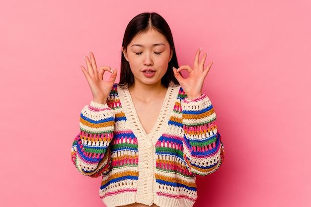 ピンクの背景に隔離された若い中国人女性は、一生懸命働いた後、リラックスしてヨガをしている.