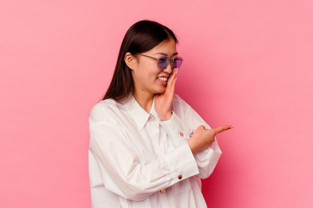Молодая китаянка изолирована на розовом фоне, говоря сплетню, указывая на сторону, сообщающую что-то.