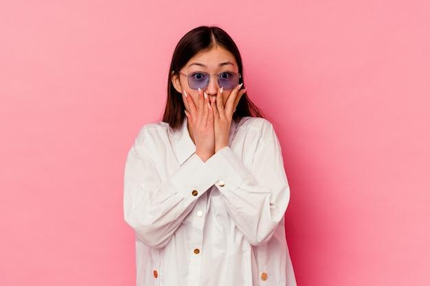 분홍색 배경에 고립 된 젊은 중국 여자는 충격을 받았고, 손으로 입을 덮고 새로운 것을 발견하고 싶어합니다.
