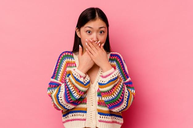 분홍색 배경에 고립 된 젊은 중국 여자 손으로 입 취재 충격.