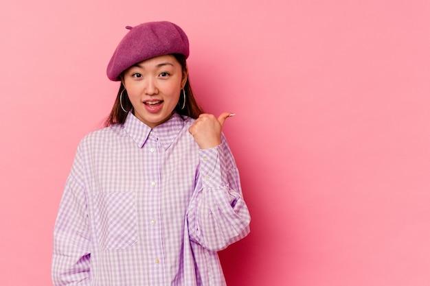 Молодая китаянка, изолированная на розовом фоне, потрясена, указывая указательными пальцами на место для копирования.
