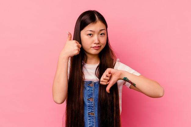 엄지 손가락과 엄지 손가락을 보여주는 분홍색 배경에 고립 된 젊은 중국 여자, 어려운 선택 개념