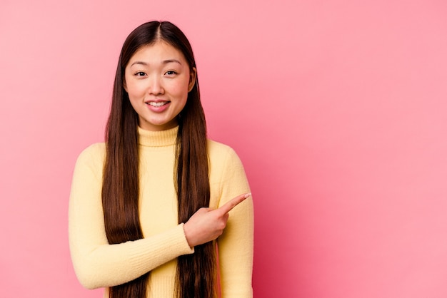 Молодая китаянка изолирована на розовом фоне, улыбаясь и указывая в сторону, показывая что-то на пустом месте.