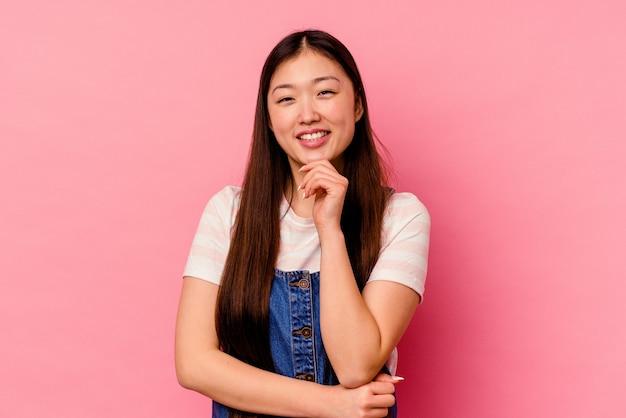 행복 하 고 자신감, 손으로 턱을 만지고 웃 고 분홍색 배경에 고립 된 젊은 중국 여자.