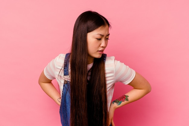 허리 통증을 겪고 분홍색 배경에 고립 된 젊은 중국 여자.
