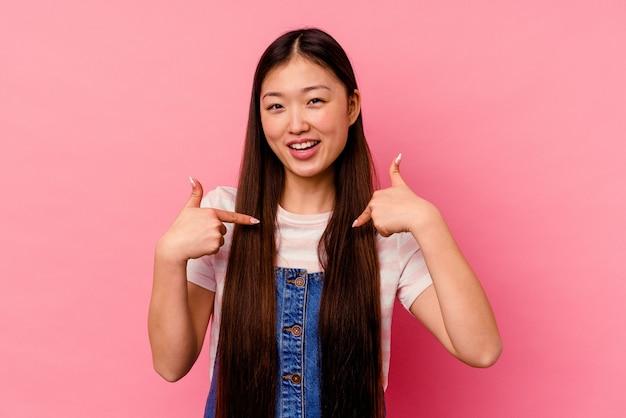 Молодая китаянка, изолированных на розовом фоне, удивлена, указывая пальцем, широко улыбаясь.